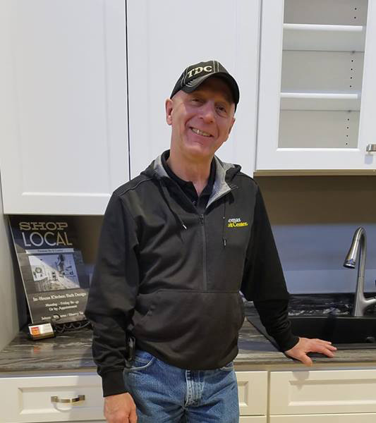Kitchen designer John Williams standing by kitchen cabinet